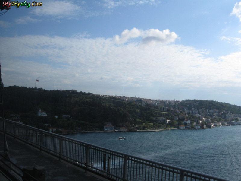 bosporus bridge,turkish flag,boat,sailing over bosporus,istanbul,turkey